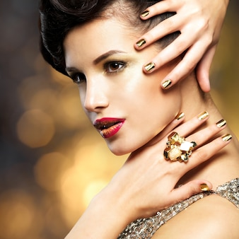 Moda linda mulher com unhas de ouro e anel de ouro no espaço de estilo