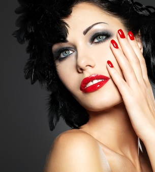Moda linda mulher com unhas vermelhas, penteado criativo e maquiagem - modelo posando