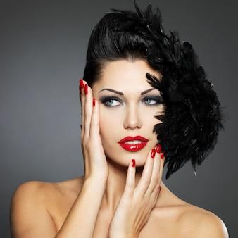 Moda linda mulher com unhas vermelhas, penteado criativo e maquiagem
