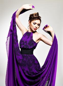 Moda linda mulher com vestido longo roxo penteado com desenho de tranças, poses no estúdio