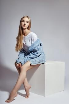 Moda loira nua senta-se em um cubo branco
