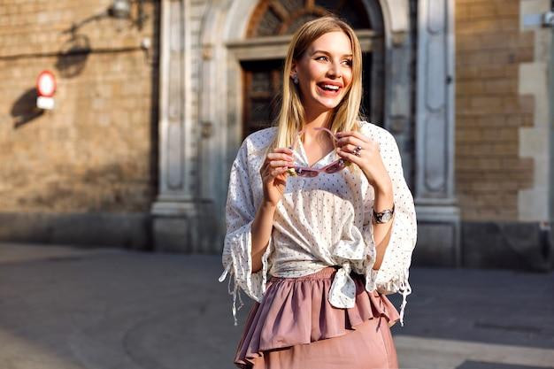 Moda luxo retrato ensolarado de mulher loira posando na rua usando blusa e saia longa de seda