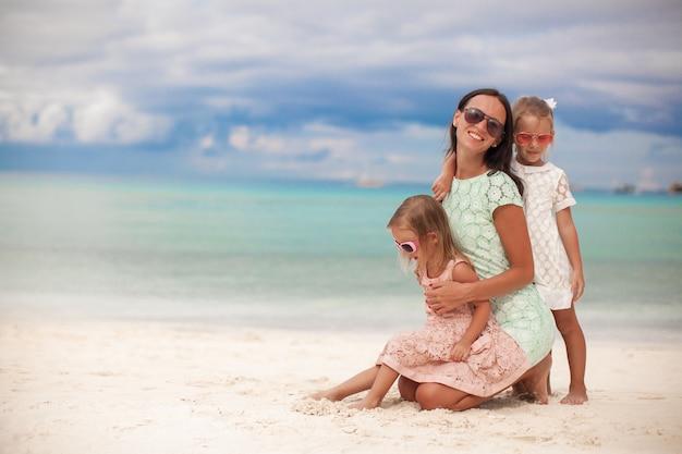 Moda mãe e duas filhas adoráveis na exótica praia em dia ensolarado