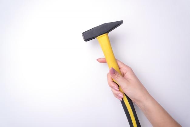 Moda mão de uma mulher com uma manicure suave detém uma ferramenta.