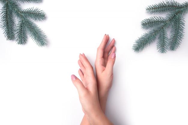 Moda, mãos femininas com manicure, unhas, galhos de árvores de natal