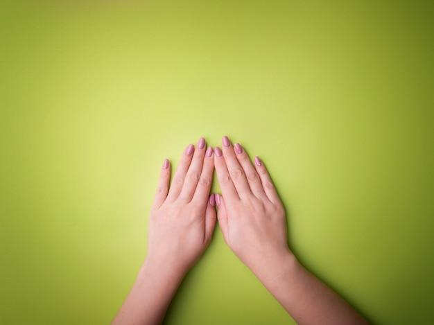 Moda, mãos femininas com manicure, unhas, pele saudável e cosméticos naturais. vista superior que contrasta contra um fundo verde.