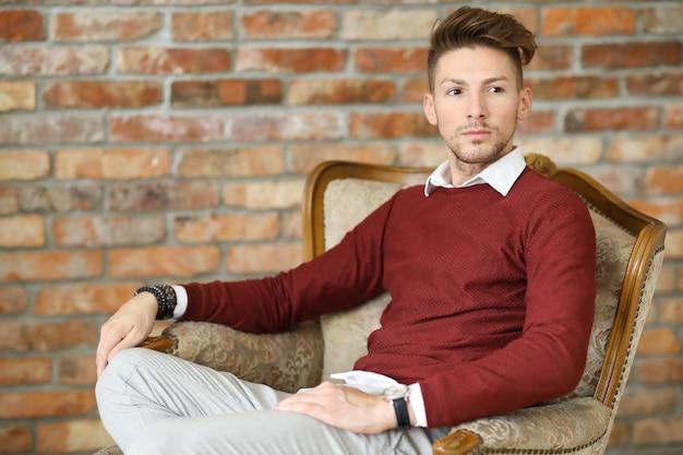 Moda masculina no chão de madeira, jovem posando