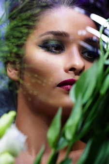 Moda menina bonita com maquiagem brilhante entre flores.