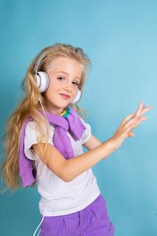 Moda menina loira com cabelos longos em camisa esporte, shorts, tênis em pé, ouvir música com fones de ouvido e danças