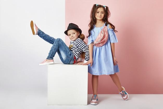 Moda menino e menina em roupas elegantes na parede colorida b
