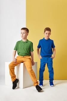 Moda menino e menina em roupas elegantes na parede colorida
