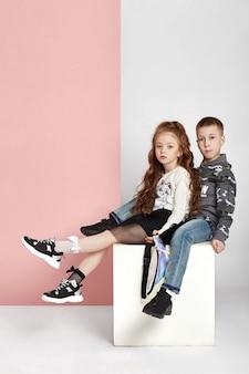 Moda menino e menina em roupas elegantes no fundo da parede colorida. roupas brilhantes de outono em crianças, uma criança posando em um fundo rosa roxo colorido. rússia, sverdlovsk, 6 de abril de 2019