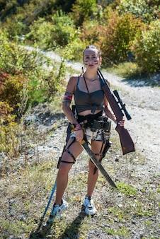 Moda militar mulher com rifle, verão quente, floresta