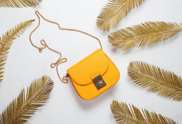 Moda minimalista ainda, vida. bolsa de couro amarela entre folhas de palmeira douradas decorativas em um fundo branco. vista do topo