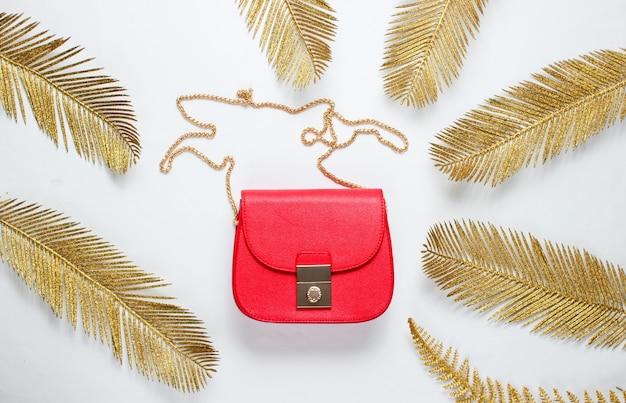 Moda minimalista ainda, vida. saco de couro vermelho entre folhas de palmeira douradas decorativas em fundo branco. vista do topo
