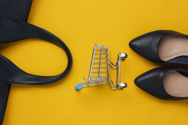 Moda minimalista e conceito de compras bolsa de carrinho de compras de couro com sapatos de salto alto em fundo amarelo