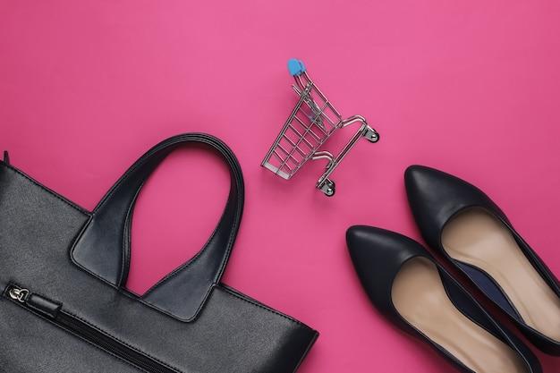Moda minimalista e conceito de compras. bolsa de carrinho de couro para sapatos de salto alto com fundo rosa