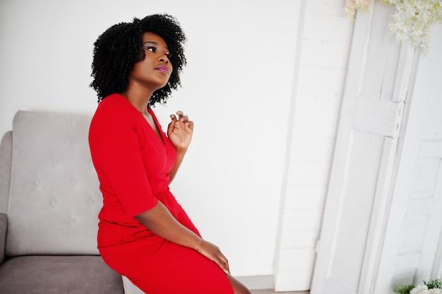 Moda modelo afro-americano em vestido vermelho beleza, mulher sexy, posando de vestido de noite na sala branca vintage.