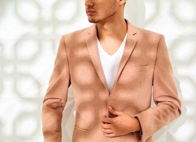 Moda modelo elegante vestido elegante terno rosa luz posando perto de parede branca
