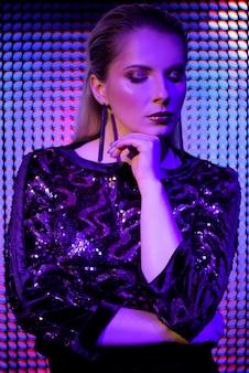 Moda modelo mulher em luzes brilhantes azuis e roxas de néon brilhante colorido uv