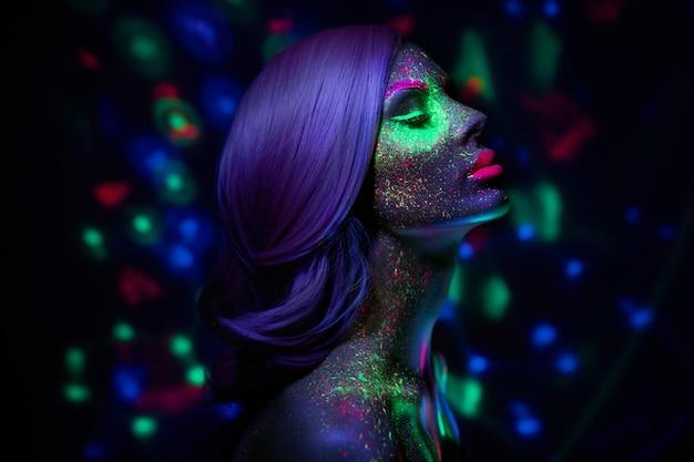 Moda modelo mulher em maquiagem fluorescente brilhante de luz de neon, cabelos longos e gotas no rosto.