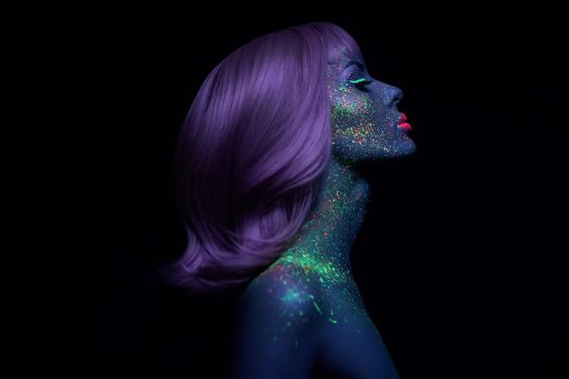 Moda modelo mulher em neon luz maquiagem fluorescente brilhante, cabelos longos, cair no rosto. menina linda de cabelo rosa modelo maquiagem colorida, pele pintada, ultravioleta de design de arte corporal
