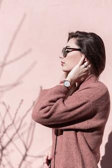 Moda modelo mulher jovem e bonita endireita o cabelo chique na rua. elegante retrato fresco adorável garota sexy na moda óculos de sol pretos com casaco elegante vintage perto da parede rosa vintage em dia ensolarado.