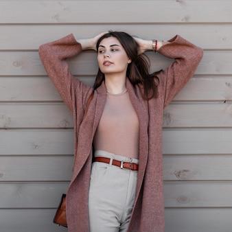 Moda modelo sexy jovem elegante em roupas da moda endireita o cabelo em pé perto de uma parede vintage na cidade. garota atraente num casaco de calças em poses de camisa na rua perto de um prédio de madeira.