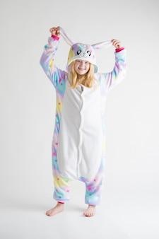 Moda moderna - linda loira posando em um fundo branco de pijama kigurumi, fantasia de coelho