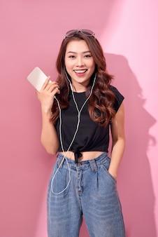 Moda muito legal garota sorridente, relaxante, ouvindo música com fones de ouvido em uma parede rosa.