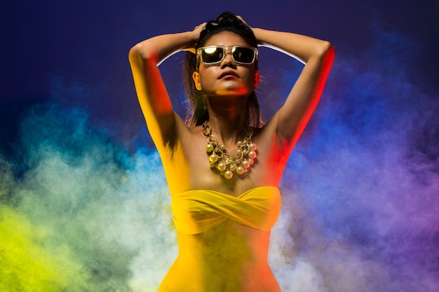 Moda mulher asiática tan pele cabelo preto bela alta moda maquiagem óculos de sol colar de pérolas acessórios usar biquíni amarelo. iluminação do estúdio fumo escuro fundo cópia espaço texto logo