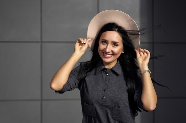 Moda. mulher bonita com cabelo longo morena lindo vestido cinza elegante, segurando o chapéu na moda em dia de vento. modelo com roupa da moda posando no fundo da parede cinza.
