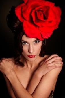 Moda mulher bonita com maquiagem brilhante e lábios vermelhos com uma grande rosa vermelha na cabeça