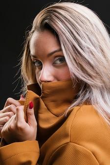 Moda mulher cobrindo a boca com jaqueta amarela