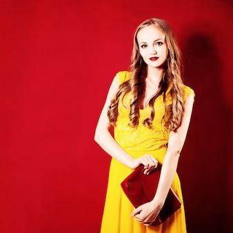 Moda mulher com cabelo loiro encaracolado. menina com vestido amarelo em fundo vermelho brilhante