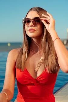 Moda mulher de biquíni vermelho, sentado perto da piscina
