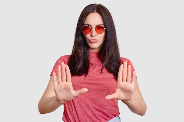 Moda mulher estar insatisfeita com algo, mostra gesto de recusa, mantém as palmas das mãos na frente, usa óculos de sol, camiseta rosa, isolado no branco. pare com isso, por favor! não me incomode