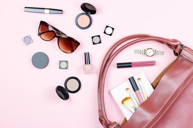 Moda mulher feminina plana leigos com produtos de beleza e acessórios na mesa-de-rosa