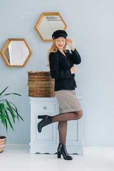 Moda mulher jovem e bonita com cabelo loiro comprido encaracolado em uma jaqueta preta e shorts xadrez fica e levanta a perna em um interior acolhedor.