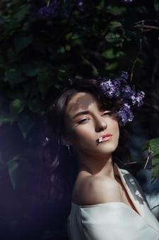 Moda mulher jovem e bonita rodeada por flores lilás