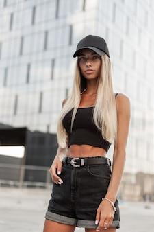Moda mulher loira hippie legal com um boné preto elegante em uma camiseta preta e shorts jeans preto caminha pela cidade perto de um edifício moderno espelho