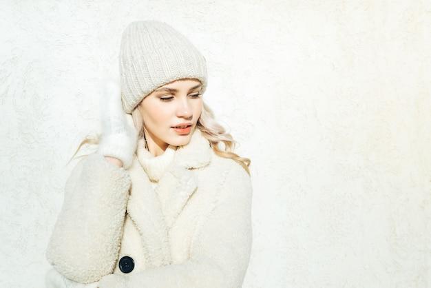 Moda mulher loira jovem com roupas de inverno em fundo de parede branca, olhando para a direita.