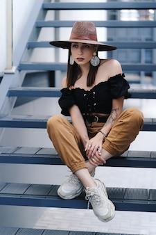 Moda mulher morena com cabelos longos, vestindo elegante chapéu de vime grande, posando nas escadas
