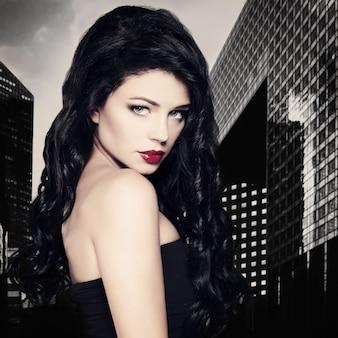 Moda mulher morena com penteado preto longo e encaracolado no fundo da cidade