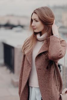 Moda mulher olha de lado, usa casaco quente na moda