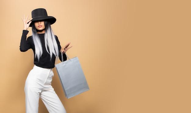 Moda mulher segura sacolas cinza de compras sobre o espaço de cópia de fundo bege amarelo, estilo de cabelo elegante menina asiática com chapéu preto calças brancas jogam bolsa prata