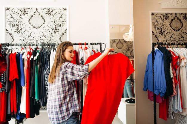 Moda mulher segurando a camisa e quer comprar elegante vestido vermelho.