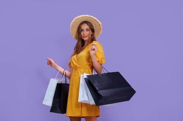 Moda mulher segurando sacolas de compras em fundo roxo.