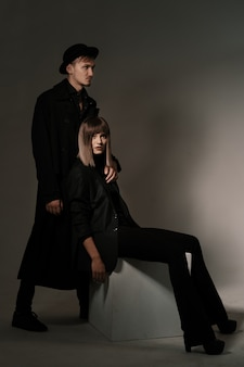 Moda mulher sentada em um cubo enquanto o homem em pé atrás dela