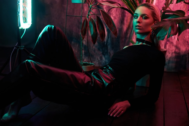 Moda mulher sentada no chão na luz de neon tropical folhagem. cabelos molhados, figura perfeita e maquiagem